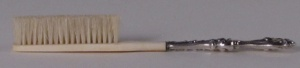 A silver-plated Edwardian toothbrush with hog bristles set in ivory (circa 1900-1908). Museum of Health Care # 010020417